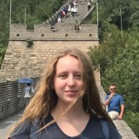 Imagen del autor. Ella está sonriendo a la cámara y de pie frente a la Gran Muralla China.