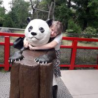 A girl (me) hugging a statue of a panda at the Berlin zoo