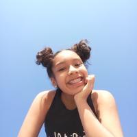 Niña sonriendo bajo el cielo