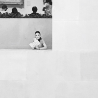 Black and white picture of girl in the window of a building