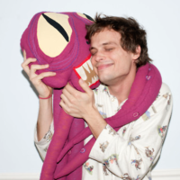 Picture of Mathew Gray Gubler-actor and author-posing by hugging a monster-looking stuffed animal