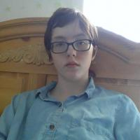 A boy with a blue shirt sitting on his bed.