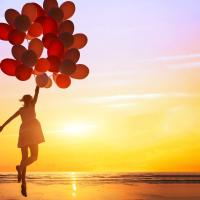 A girl holding a bunch of balloons jumping with happiness. She stands on a beach with a beautiful sunset in the background.