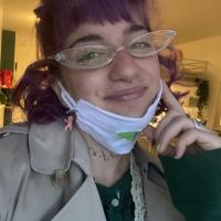 The image shows a purple haired smiling women with small glasses, bangs and a face mask that is resting over her chin