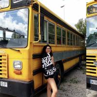 A gril smiling in front of an school bus
