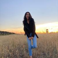 Profile picture of the writer: female young adult smiling at the camera, dressed in some light blue jeans and a black leather jacket. She is a dark-haired individual with wavy, long hair and dark brown eyes, currently standing up on one of her feet in the middle of a field. A beautiful sunset serves as the background of the described photograph.