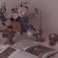A big vase of white and red roses, an open book and a candle